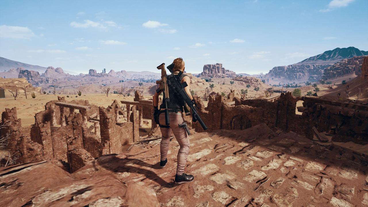 Personagem armado de PUBG na parte alta de ruínas, observando o cenário desértico