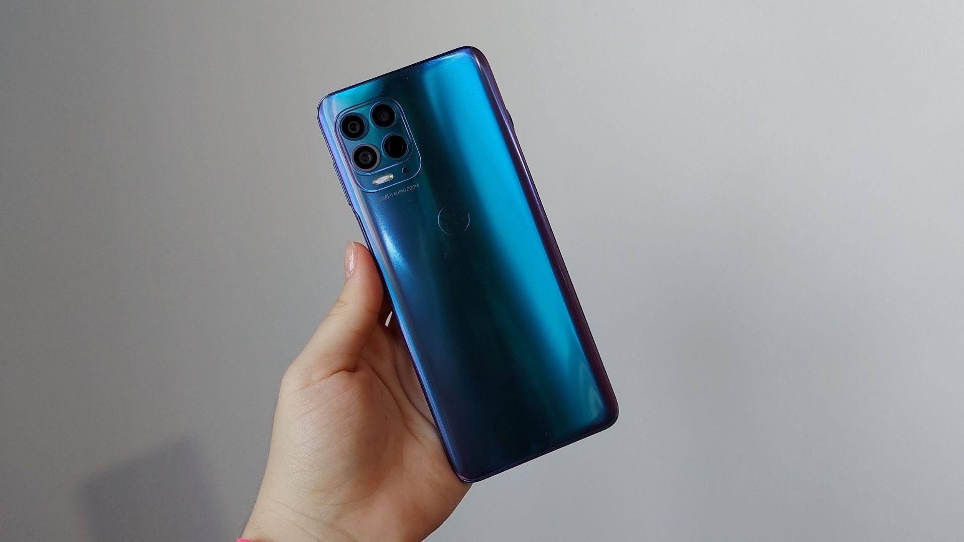 Mão segurando Moto G100 e exibindo parte traseira do celular