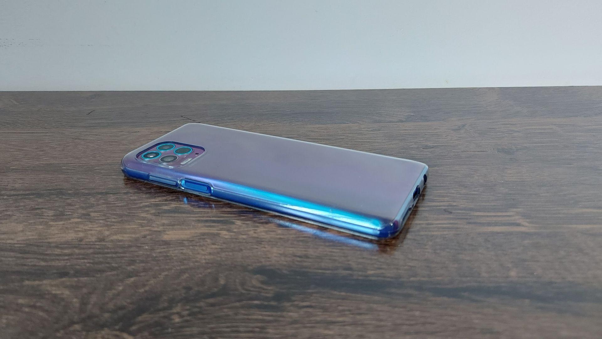 Moto G100 em cima de uma mesa de madeira e com parte traseira virada para cima e ângulo diferente