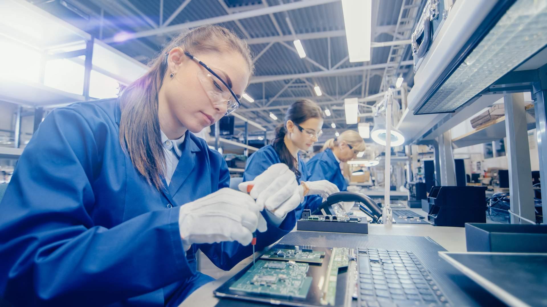 Várias mulheres brancas em uma fábrica de notebooks