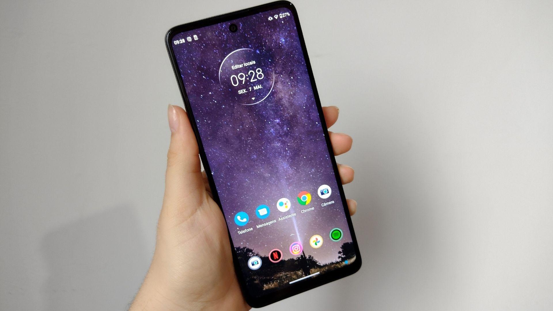 Imagem mostra mão segurando Moto G60 e exibindo parte frontal do celular